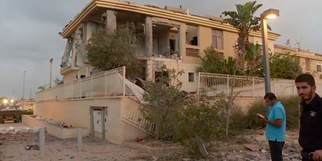 In this image made from video, police inspect the damage to a building from a rocket, Wednesday, Oct. 17, 2018, in Beersheba, Israel. The Israeli military says a rocket fired from Gaza made a direct hit on a home in southern Israel.
