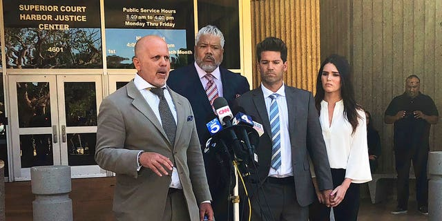 Reality show doctor Grant Robicheaux, second from right, and his girlfriend, Cerissa Riley, listen as Robicheaux's attorney, Philip Cohen, left, speaks outside court in Newport Beach, California.