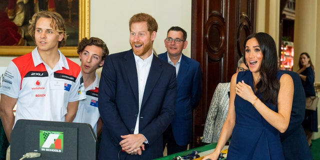 The Duke and Duchess of Sussex start model Formula 1 cars during a demonstration at a reception given by the Governor of Victoria at Government House during their visit to Melbourne, Australia, Thursday, Oct. 18, 2018. Prince Harry and his wife Meghan are on day two of their 16-day tour of Australia and the South Pacific. (Dominic Lipinski/Pool via AP)