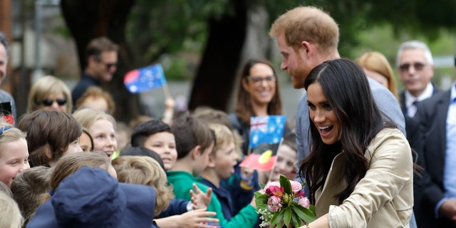 Britain's Prince Harry and Meghan, Duchess of Sussex greet children during a visit to Albert Park Primary School in Melbourne, Australia, Thursday, Oct. 18, 2018. Prince Harry and his wife Meghan are on day three of their 16-day tour of Australia and the South Pacific.(AP Photo/Kirsty Wigglesworth,Pool)