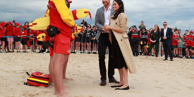 Britain's Prince Harry and Meghan, Duchess of Sussex talk to life guards at South Melbourne Beach in Melbourne, Australia, Thursday, Oct. 18, 2018. Prince Harry and his wife Meghan are on day two of their 16-day tour of Australia and the South Pacific. (Ian Vogler/Pool Photo via AP)