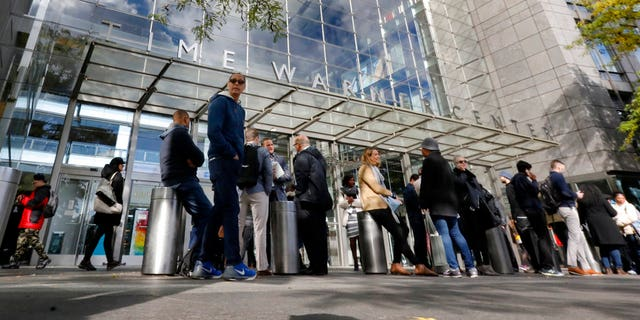 People gather outside the Time Warner Center, in New York, Wednesday, Oct. 24, 2018. A police bomb squad was sent to CNN's offices in New York City and the newsroom was evacuated because of a suspicious package. (AP Photo/Richard Drew)