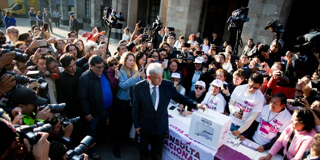Mexico's President-elect Andres Manuel Lopez Obrador casts his vote on whether to continue with the $13 billion airport to replace the current Benito Juarez International Airport in Mexico City, Thursday, Oct. 25, 2018. The future of Mexico City's new airport, already about a third completed, comes down to a public vote this week in a political high-wire act by the country's president-elect that could shut down Mexico's largest infrastructure project in recent memory. Lopez Obrador promised to let the people decide the fate of the airport. (AP Photo/Eduardo Verdugo)