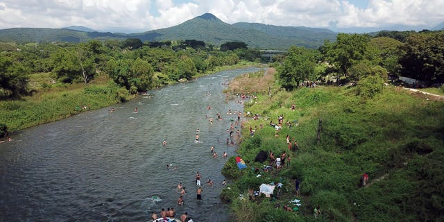 Honduran migrants take a bath in a river in Pijijiapan, Mexico, Thursday, Oct. 25, 2018. Thousands of Central American migrants renewed their hoped-for march to the United States on Wednesday, setting out before dawn with plans to travel another 45 miles (75 kilometers) of the more than 1,000 miles that still lie before them. (AP Photo/Rodrigo Abd)