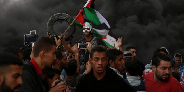Protesters chant slogans while waves their national flags as others burn tires near the fence of the Gaza Strip border with Israel during a protest east of Gaza City, Friday, Oct. 26, 2018. (AP Photo/Adel Hana)