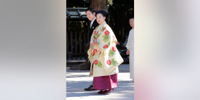 Japanese Princess Ayako, front, the third daughter of the late Prince Takamado, dressed in traditional ceremonial gown, and Japanese businessman Kei Moriya, rear, arrive at Meiji Shrine for their wedding ceremony in Tokyo, Monday, Oct. 29, 2018.(Kyodo News via AP)