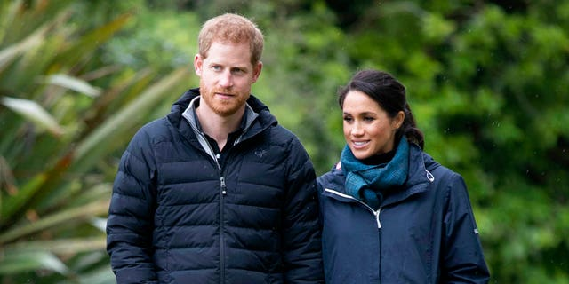 Prince Harry and Duchess Megan walk together at Abel Tasman National Park in New Zealand on Monday.