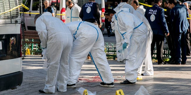 Tunisian forensic experts work on the scene of an attack after a 30-year-old woman blew herself on the Habib Bourguiba avenue in Tunis, Tunisia. (AP Photo/Riadh Dridi)
