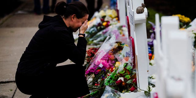 A woman pays her respects at a makeshift memorial in the aftermath of a deadly shooting at the Tree of Life Synagogue in Pittsburgh, Monday