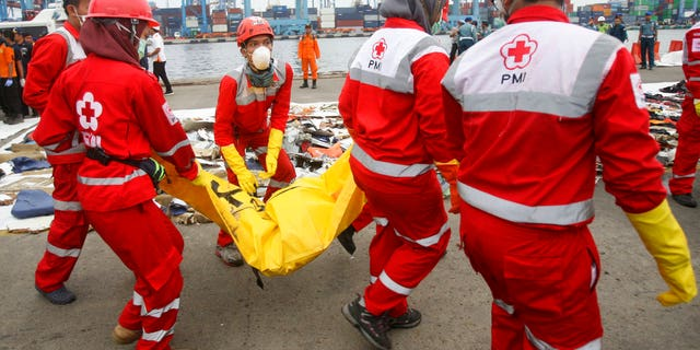 Rescuers carry a body bag containing the remains of victims retrieved from the waters where Lion Air flight JT 610 is believed to have crashed at Tanjung Priok Port in Jakarta, Indonesia.