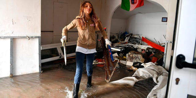 A woman cleans up debris from a flooded room a day after a storm, in Boccadasse, northern Italy, Tuesday, Oct. 30, 2018. (Luca Zennaro/ANSA via AP)