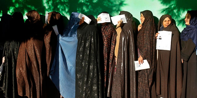Women line up outside a polling station during the parliamentary election in western Herat city, Afghanistan, on Saturday. (AP Photo/Hamed Sarfarazi)