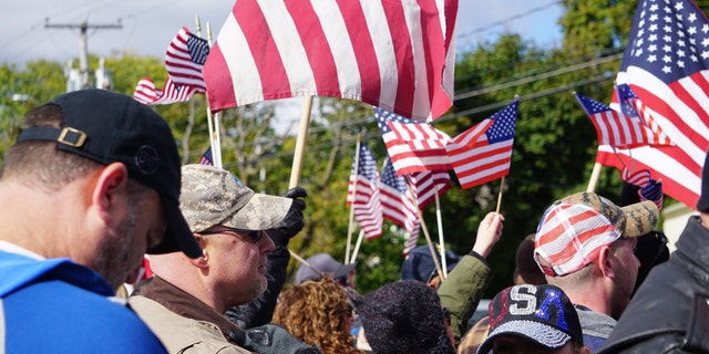 """Supporters wave flags at the """"American flag appreciation walk"""" in New Paltz, New York Sunday afternoon."""