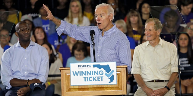Former Vice President Joe Biden gestures as Florida Democratic gubernatorial candidate Andrew Gillum, left, and U.S. Sen. Bill Nelson, D-Fla., right, look on during a campaign rally for Gillum and Nelson on Monday in Tampa, Fla. (AP Photo/Chris O'Meara)