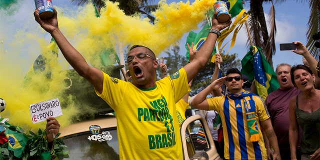 Supporters of Jair Bolsonaro singing the national anthem in front of his house during the presidential runoff election in Rio de Janeiro, Brazil, on Sunday. (AP Photo/Silvia Izquierdo)