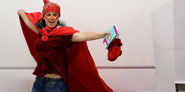 A woman donning the official Workers' Party color celebrates after voting in the presidential runoff election in Sao Paulo, Brazil, on Sunday. (AP Photo/Nelson Antoine)