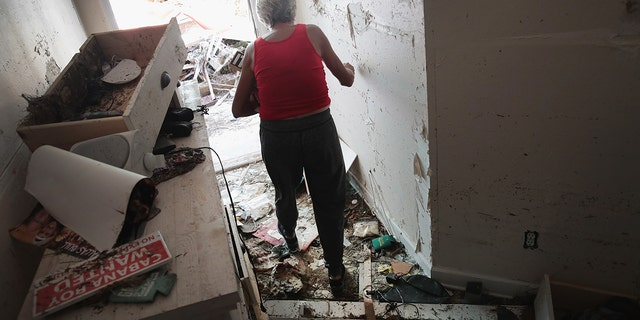 Luke Bryan's mother moves through the rubble of her home after Hurricane Michael.