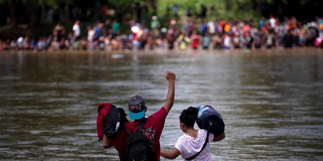 A migrant raised his fist as he neared the Mexican side of the Suchiate River, that connects Guatemala and Mexico. (AP Photo/Santiago Billy)