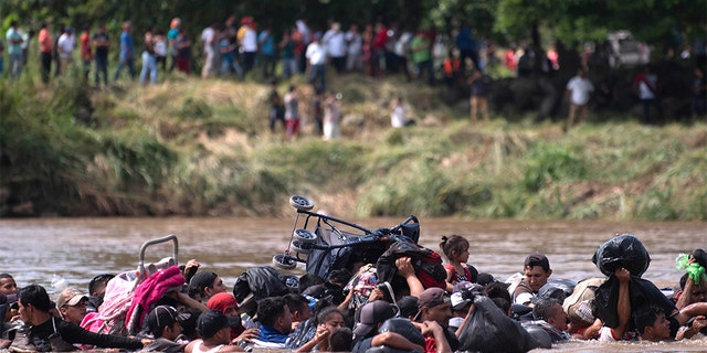 A group of Central American migrants wading across the Suchiate River. (AP Photo/Santiago Billy)