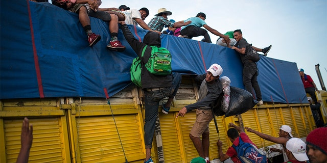 Migrants climbing on a truck to ride on the road that connects Tatanatepec with Niltepec, Mexico. (AP Photo/Rodrigo Abd)