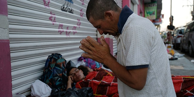 Marvin Sanabria, a Central American migrant traveling with a caravan to the U.S., kneels in prayer after waking up, in Huixtla, Mexico, Tuesday, Oct. 23, 2018. The caravan, estimated to include more than 7,000 people, had advanced but still faced more than 1,000 miles, and likely much further, to the end of the journey. (AP Photo/Moises Castillo)