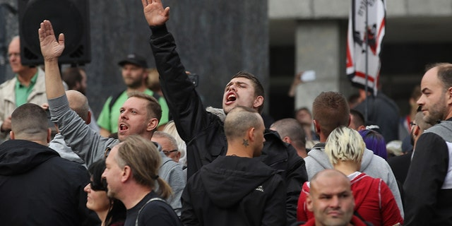 A man raises his arm in a Heil Hitler salute towards heckling leftists at a right-wing protest gathering the day after a man was stabbed and died of his injuries on August 27, 2018 in Chemnitz, Germany