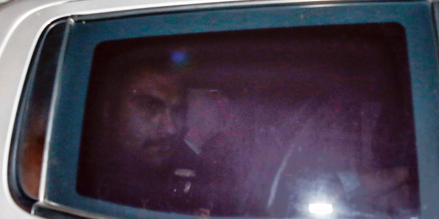 Pastor Andrew Brunson, center, sits inside a car as he arrives for his trial in Izmir, Turkey, early Friday.,