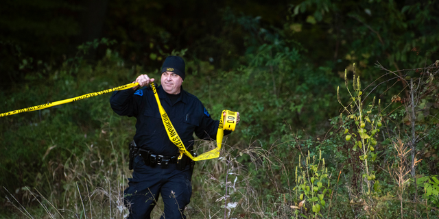 In this Monday, Oct. 22, 2018 photo, detectives investigate the scene where remains believed to be those of a southwestern Michigan woman who disappeared in 2010 were found, in Fulton, Michigan.