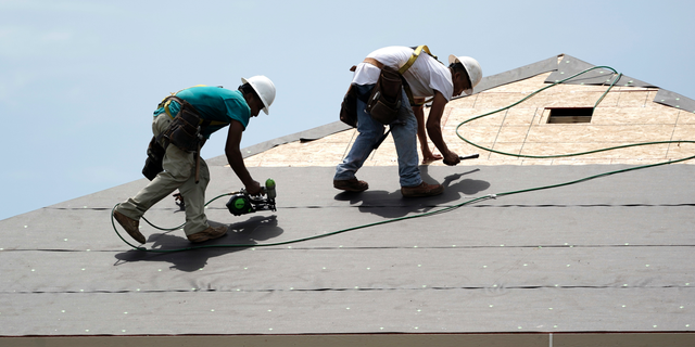 FILE- In this July 23, 2018, file photo construction workers put down roofing paper on home in Houston. General contractors and other small businesses in the home remodeling industry can expect revenue to slow in 2019, the result of rising mortgage rates and sluggish home sales. That's the prediction of Harvard University's Joint Center for Housing Studies, which last week issued its quarterly report on home remodeling. (AP Photo/David J. Phillip, File)