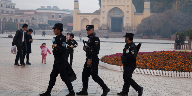 "In this Nov. 4, 2017 file photo, Uighur security personnel patrol near the Id Kah Mosque in Kashgar in western China's Xinjiang region. China's northwestern region of Xinjiang has revised legislation to allow the detention of suspected extremists in ""education and training centers."" (AP Photo/Ng Han Guan, File)"