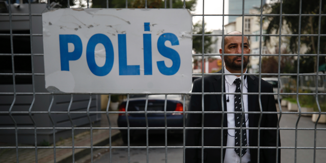 """A security guard stands behind barriers blocking the road leading to Saudi Arabia's consulate in Istanbul, Saturday, Oct. 20, 2018. Turkey will """"never allow a cover-up"""" of the killing of Saudi journalist Jamal Khashoggi in Saudi Arabia's consulate in Istanbul, a senior official in Turkey's ruling party said Saturday after Saudi Arabia announced hours earlier that the writer died during a """"fistfight"""" in its consulate. (AP Photo/Emrah Gurel)"""