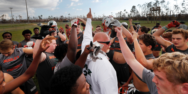 Mosley High head coach Jeremy Brown leads practice outside the heavily damaged school in the aftermath of Hurricane Michael in Lynn Haven, Fla., Friday, Oct. 19, 2018. (AP Photo/Gerald Herbert)