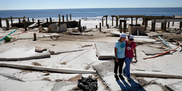 FILE - In this Oct. 12, 2018, file photo, Joy Hutchinson, left, is comforted by her daughter Jessica Hutchinson, as she returns to find her home swept away from hurricane Michael in Mexico Beach, Fla.  The tropical weather that turned into monster Hurricane Michael began as a relatively humble storm before rapidly blossoming into the most powerful cyclone ever to hit the Florida Panhandle, causing wrenching scenes of widespread destruction.(AP Photo/David Goldman, File)