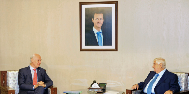"""In this photo released by the Syrian official news agency SANA, Syria's Foreign Minister Walid al-Moallem, right, meets with U.N. Special Envoy for Syria Staffan de Mistura, in Damascus, Syria, Wednesday, Oct. 24, 2018. Syrian state media said al-Moallem has told the U.N. envoy that the constitution is a """"sovereign"""" matter and Damascus will not allow any foreign intervention regarding it. (SANA via AP)"""