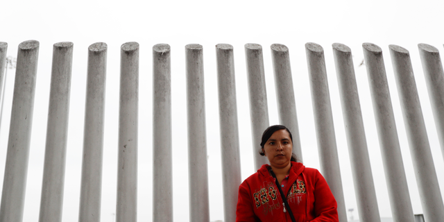 In this Oct. 23, 2018 image, Ana Delia Soto Duarte, who seeks asylum in the United States from her home in Guerrero, Mexico, waits in hopes of hearing her number called to cross the border in Tijuana, Mexico.