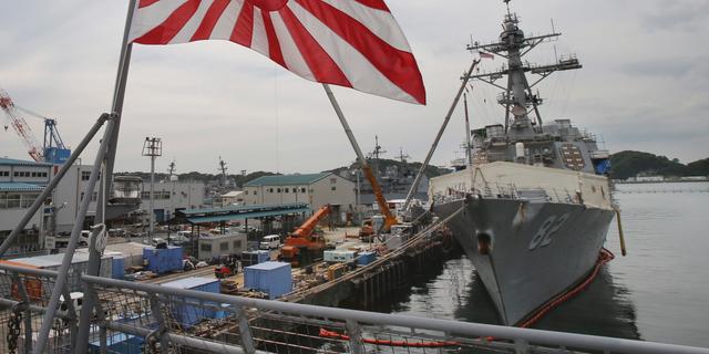 Japan's military flag, Risi ng Sun Flag, flutters on Japan's Maritime Self-Defense Force tanker JS Kunisaki anchored in Yokosuka, near Tokyo, in this May 27, 2014, file photo.