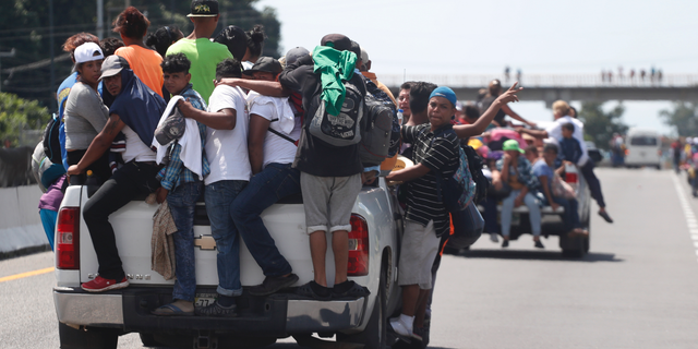 Central American migrants making their way to the U.S. in a large caravan cling to the trucks of drivers who offered them free rides, as they arrive to Tapachula, Mexico.