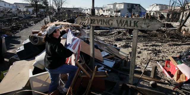 In this Nov. 14, 2012 photo, Louise McCarthy places an American flag on a street sign for Irving Walk in the Breezy Point neighborhood of Queens, N.Y. The sign survived a fire that swept through the seaside community during Superstorm Sandy two weeks earlier. Six years later, most residents have stayed. Homes have been restored, and Sandy led to a new ferry service and a rebuilt boardwalk.  (AP Photo/Mark Lennihan)