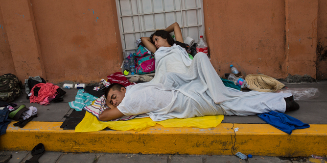 A migrant woman slowly begins to wake after sleeping on a sidewalk in Tapanatepec, Mexico, Sunday, Oct. 28, 2018. Thousands of migrants who are part of a caravan of Central Americans trying to reach the U.S. border took a break Sunday on their long journey toward the U.S. border.