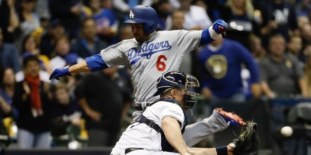 FILE - Los Angeles Dodgers' Brian Dozier scores past Milwaukee Brewers catcher Erik Kratz during the fifth inning of Game 6 of the National League Championship Series baseball game Friday.