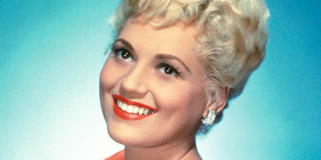 Judy Holliday (1921-1965) in a studio portrait, against a bluw background, circa 1950.