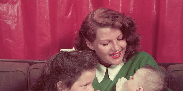 Rita Hayworth sitting on a sofa with her young daughters, Rebecca Welles (left) and Yasmin Khan, in her lap.