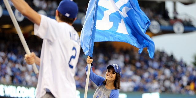Mila Kunis and Ashton Kutcher wave Dodgers flags prior to Game 6 of the 2017 World Series between the Houston Astros and the Los Angeles Dodgers at Dodger Stadium on Tuesday, October 31, 2017 in Los Angeles, California.