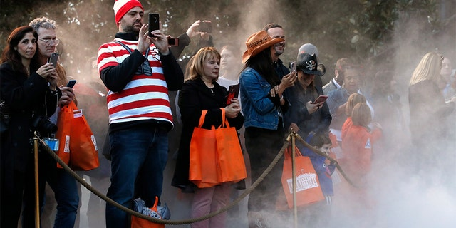 Parents taking photographs of their children in Halloween costumes, as mist from a fog machine rose around them, during a trick-or-treat event with President Donald Trump and first lady Melania Trump at the White House.