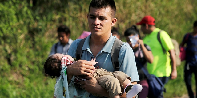 A young man carries a child in the Hondurans' caravan.