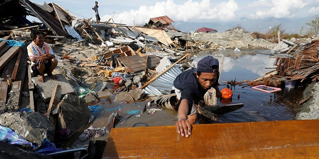 ,A family searches for their belongings in the remains of their home in the Petobo neighborhood which was hit by an earthquake, in Palu, Central Sulawesi, Indonesia, Oct. 10, 2018.