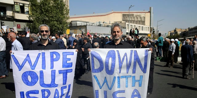 Two Iranian worshippers hold up anti-American and anti-Israeli placards, in a rally to condemn Saturday's terror attack in Ahvaz, after Friday prayers in Tehran, Iran, Friday, Sept. 28, 2018.