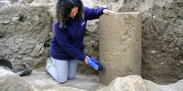 Danit Levy, Director of the excavations on behalf of the Israel Antiquities Authoritybeside the inscription as found in the field. (Photo: Yoli Shwartz, IAA)