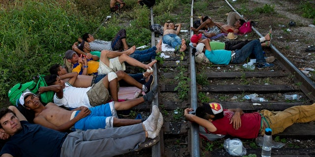 "Central American migrants rest on the train tracks where the freight train known as ""The Beast"" has for decades carried migrants north, as a thousands strong caravan travel on foot and by road stops between Pijijiapan and Arriaga, Chiapas state in Mexico."