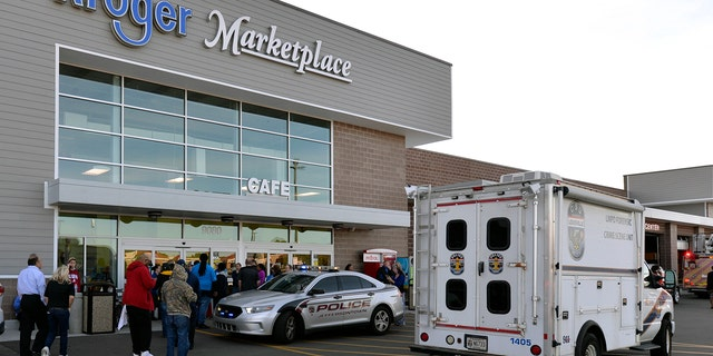 Employees wait outside the entrance of a Kroger grocery following a shooting that left two people dead and a suspect in custody, Wednesday, Oct. 24, 2018, in Jeffersontown, Ky. A man fatally shot another man inside a Kroger grocery store, shot and killed a woman in the parking lot, and then exchanged fire with an armed bystander who intervened before he fled the scene on the outskirts of Louisville, Kentucky, on Wednesday, police said. He was captured shortly afterward. (AP Photo/Timothy D. Easley)